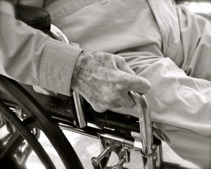 black and white pic of an elderly man sitting in a wheelchair