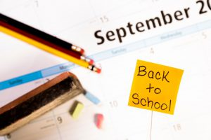 back to school post it note with school materials around.