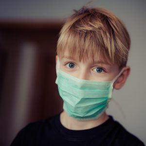 caucasian boy with blonde hair wearing a blue surgical mask.
