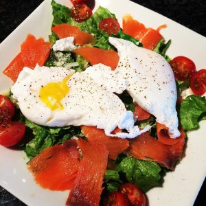 salad with lox and fried egg on top with yolk coming out.