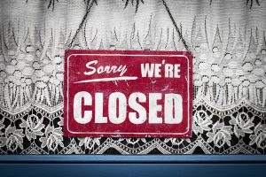"red sign with ""sorry we're closed"" in white"