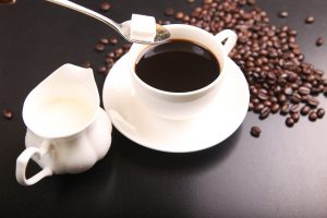 black coffee in a white up and saucer with a sugar cube in a spoon over the cup, and coffee beans on the table