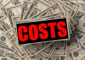 """a sign that says """"costs"""" in red over a pile of 10 dollar bills."""