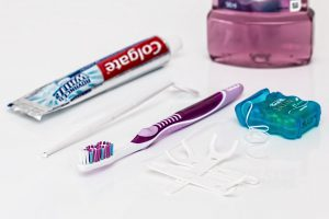 toothpaste, toothbrush, and floss all lined up on a white table.