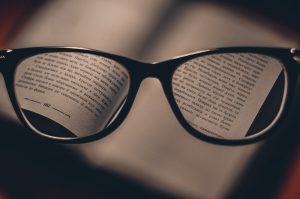 glasses with words on each lens from a book in the background