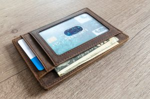 brown leather wallet with clear screen showing card and money in it