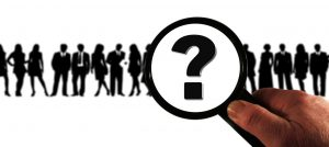 silhouette of a group of people with a magnifying glass over them with a question mark in it.