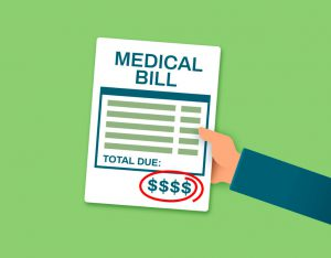 "hand holding a paper that says ""medical bill"" on it with dollar signs on the bottom circled in red."