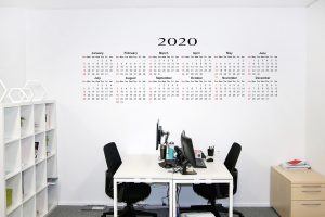 large wall calendar on the wall above a table with two black chairs.