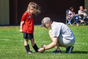 caucasian dad kneeling down to tie his daughters cleat., who is in soccer uniform.