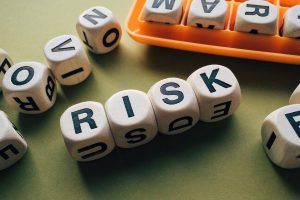 the word risk spelled out on scrabble dice