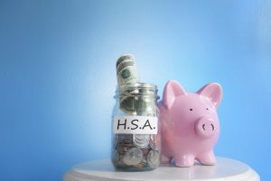 pink piggy bank next to a jar that has money in it labeled HSA