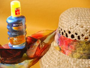 sunscreen spf 30 bottle next to a hat