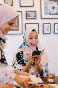woman with hijab on looking at her phone smiling