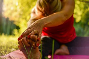 caucasian woman sitting on a yoga mat outside stretching and grabbing her feet.