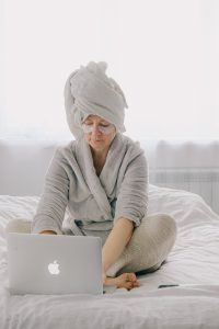 older caucasian woman sitting in a robe with a towel on her head looking at her laptop