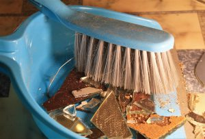blue dustpan and brush with glass in the dustpan