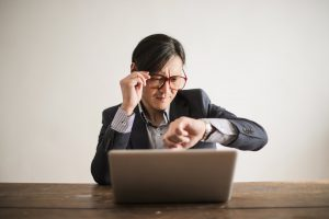 asian man looking at his watch while holding his glasses and sitting in front of a laptop