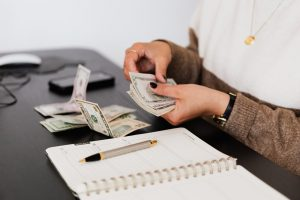 womans hands counting money at a table with a pen and notebook in front of her.