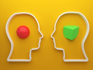 picture of two silhouettes with a red ball in one mind and a green cube in the other