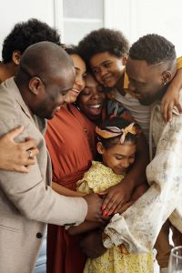 african american family in a huddle hugging.