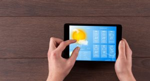 hand-checking-weather-on-tablet