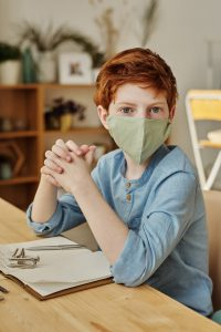 caucasian child with red hair sitting at a desk with a mask on
