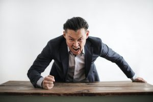 asian man in a suit standing up and pounding his fist on a table in rage.