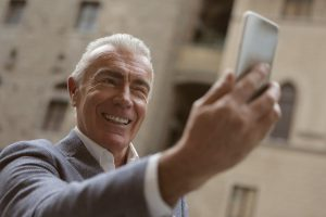 older caucsasian man holding a cell phone up smiling