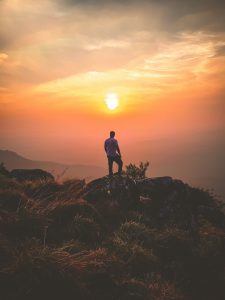 man standing at a cliff while the sun sets