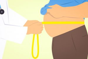 doctors hands wrapping a measuring tape around a mans belly.