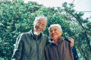 older asian man and woman smiling with the mans arm around the woman's shoulder