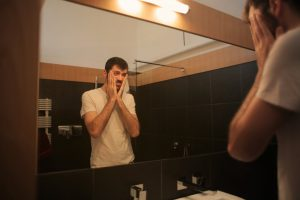 man standing in the mirror holding his cheeks with both hands