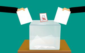people's hands putting a sheet of paper in a ballot box