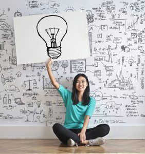 woman sitting down with a light bulb drawn on a paper holding it over her head.