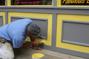 man kneeling down painting the outside of a building yellow and gray