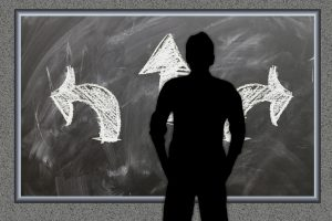 silhouette of a person standing in front of 3 arrows pointing in 3 different directions