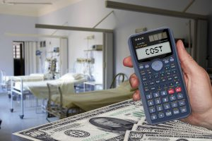 calculator with the word cost on it with a hospital bed in the background and money below the calculator