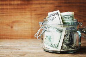 hundred dollar bills in a glass jar