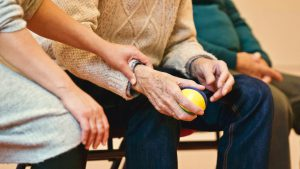 older mans lower half of body sitting down holding a ball in his hand with a person holding his arm in support