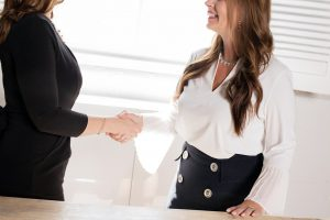 two women in business attire shaking hands