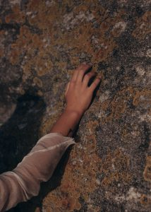 caucasian hand touching a wall with mold all over it
