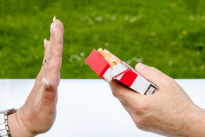 caucasian hand turning down a cigarette from a box being held by someone else