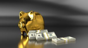 gold piggy bank with stacks of money next to it