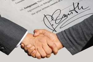 two hands shaking with a piece of paper in the background that is signed