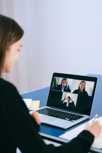 caucasian woman in front of a laptop with people on the screen