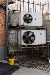 two white ventilation systems , one on top of another.