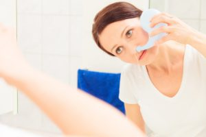 caucasian woman flushing her nose with a white neti pot