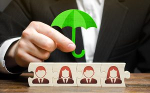 torso of a person with a suit in holding a green umbrella over blocks with peoples silhouettes on them