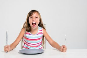 caucasian little girl sitting at a table with a fork and knife in her hand while screaming
